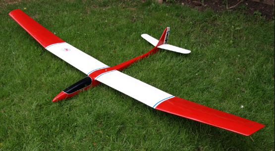 A remote-controlled red and white glider resting on the ground atop some grass.