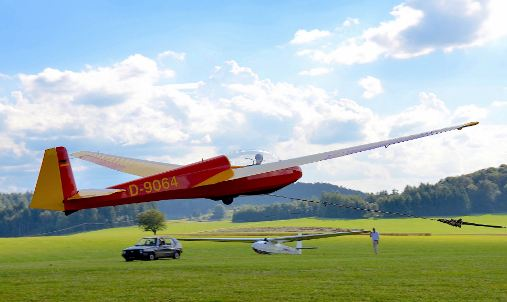An ASK 13 sailplane being launched using a winch in an open field and in view of a car and another sailplane.