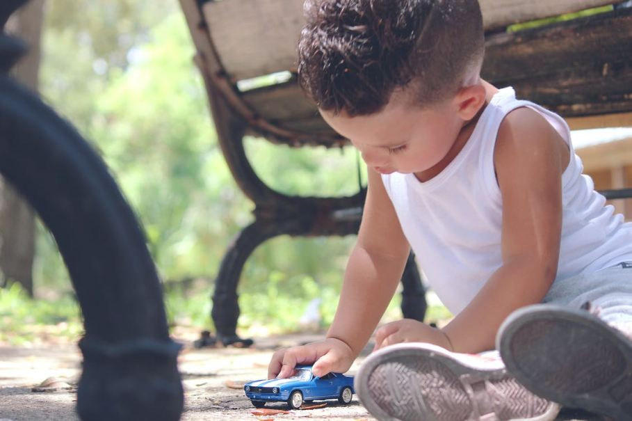 boy-in-white-tank-top-playing-blue-coupe-die-cast-near-brown-wooden-bench-chair-during-daytime