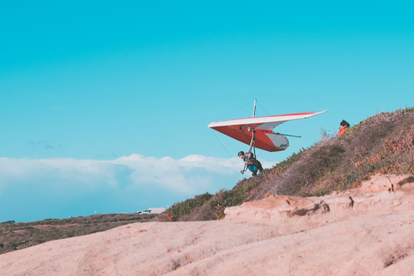 A man on a hill with a glider