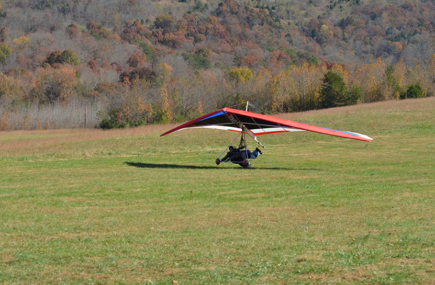 green grass, two people flying, landing of a hang glider