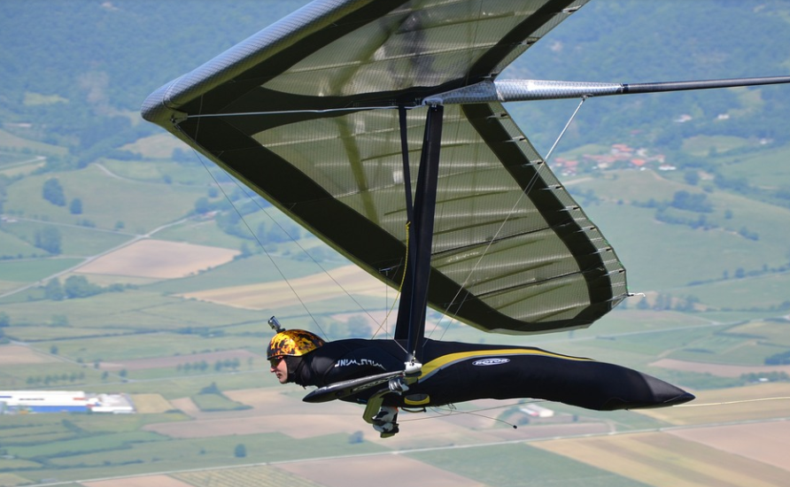 a person hang gliding, large hang glider, large fields