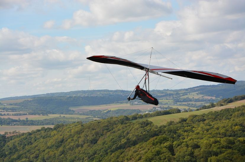 glider in a black and red gear, green trees and mountains, cloudy sky